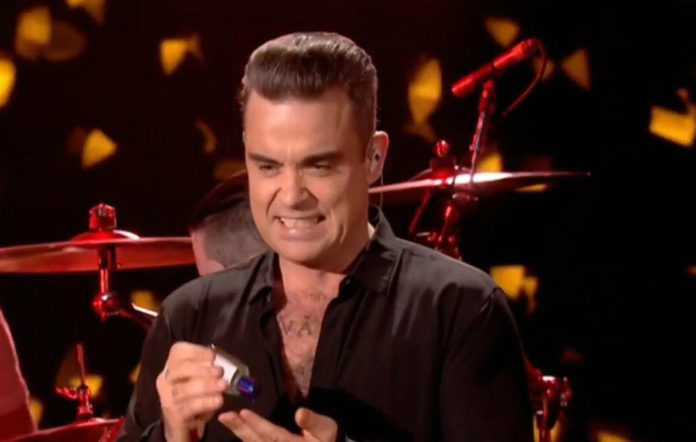 Robbie Williams uses hand sanitiser after shaking hands with fans