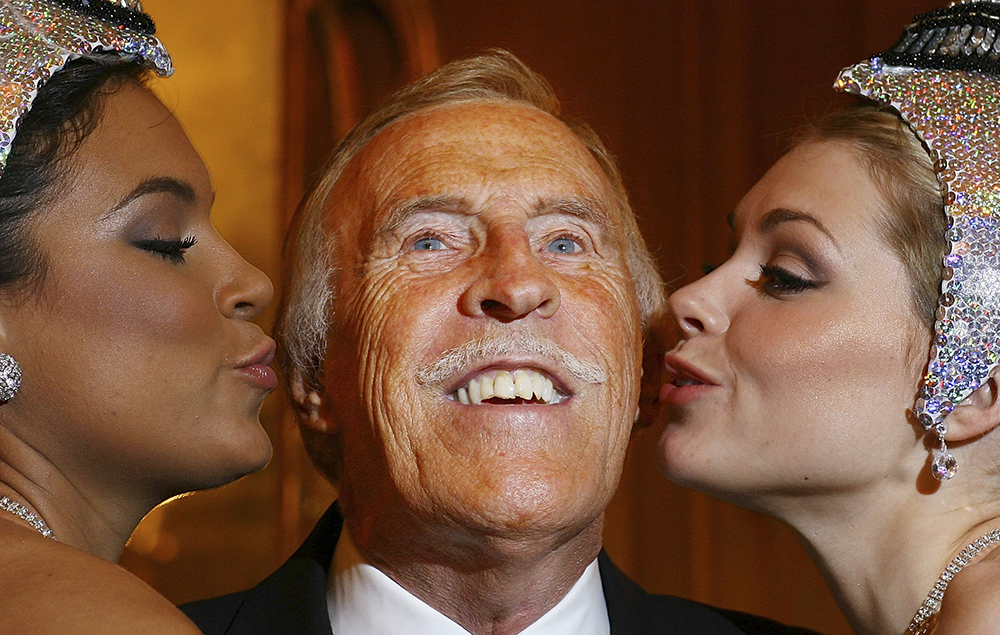 Bruce Forsyth poses at his 80th birthday press conference with Miss Puerto Rico (L) and Miss Great Britain