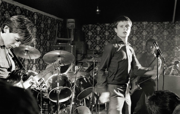 L-R: Bernard Sumner, Ian Curtis, Peter Hook performing live onstage at Bowdon Vale Youth Club