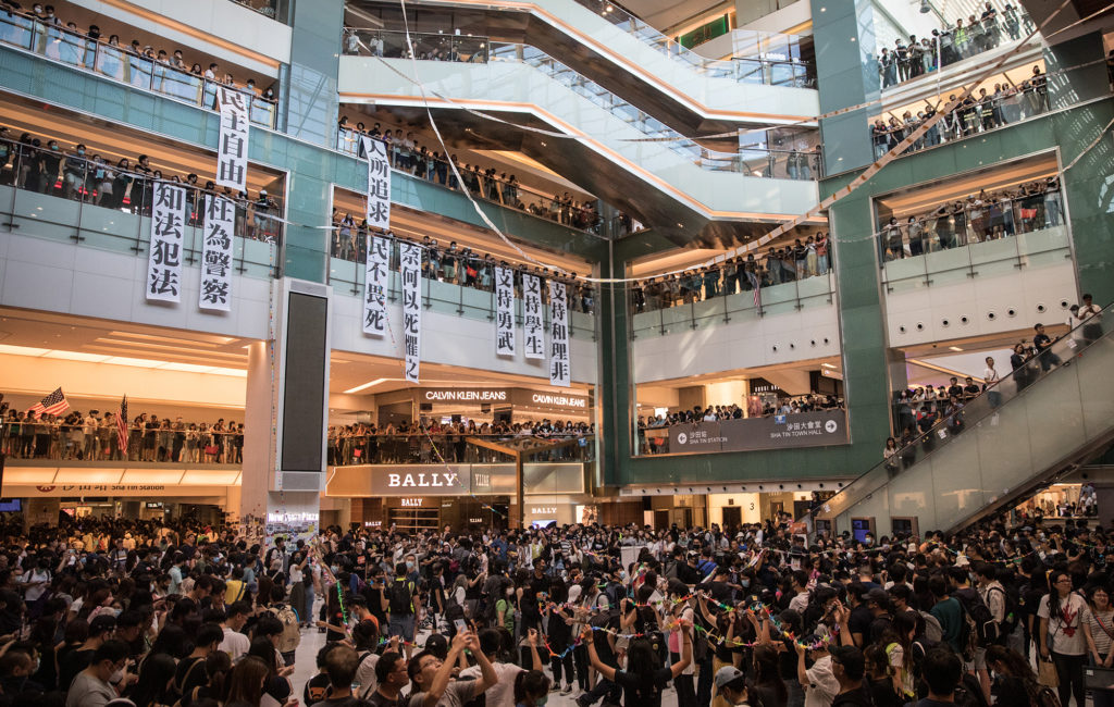 Pro-democracy protesters sing songs and chant slogans during a rally inside a shopping mall in Shatin on September 22, 2019