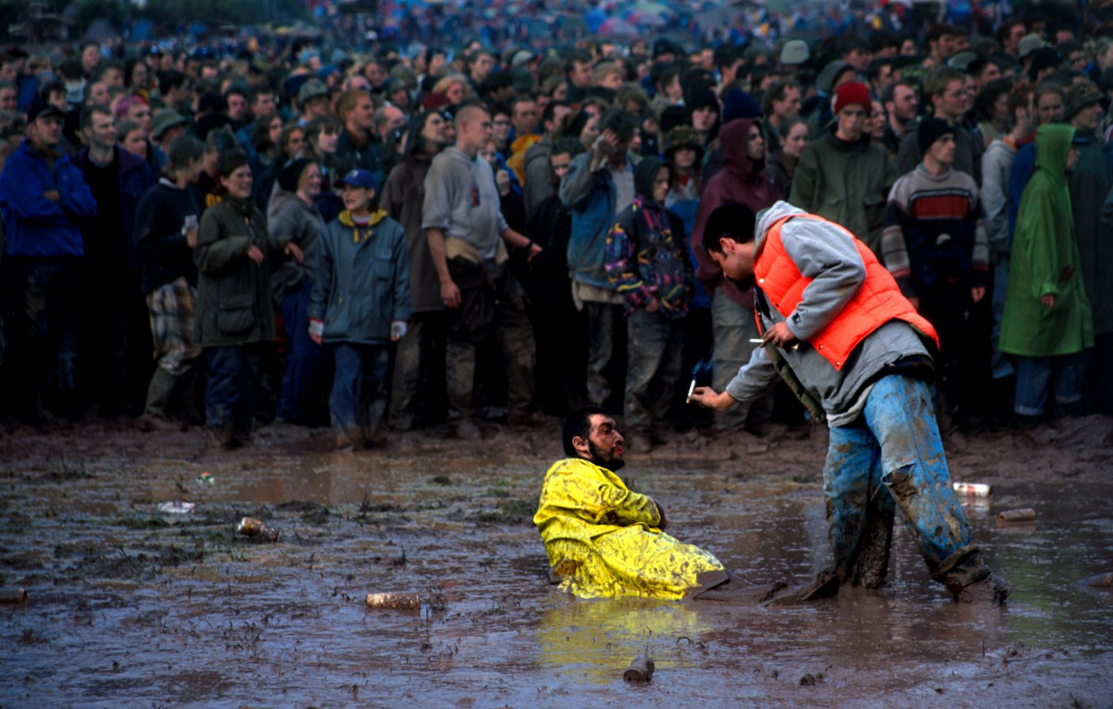 A 90s festival-goer delivers vital provisions to a friend stuck in the mud. Credit: Ann Cook