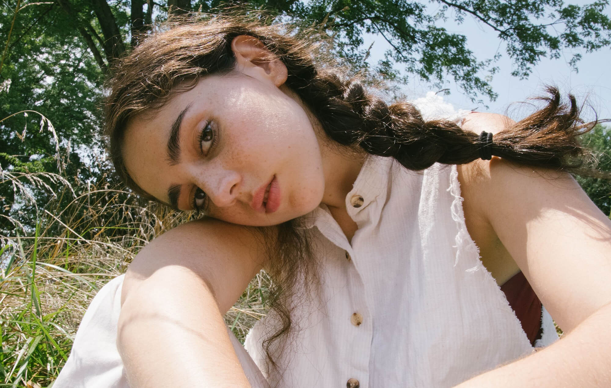 Photograph of Samia, a light-skinned young woman in her early twenties with thick dark eyebrows and long brown braided hair. She is wearing a white sleeveless buttoned shirt and is tilting her head to the right so it's resting on her arm and looking at the camera.