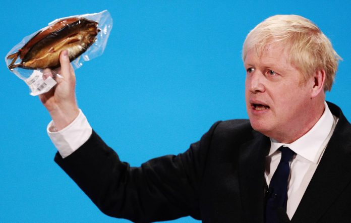 Boris Johnson holds a kipper (smoked fish) as he talks at the final hustings of the Conservative leadership campaign at ExCeL London on July 17 (Photo by Dan Kitwood/Getty Images)